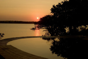 Sundowners down by the pool overlooking the lake where hippos grunt is a highly recommended activity